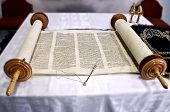 foto of circumcision  - Torah scrolls are on the table with a stick read cape to scroll and kolokolchiki in Hebrew the ancient language picture sdelanaya close - JPG