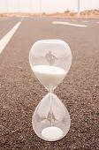 foto of time-bomb  - Time Concept Alarm Hourglass on the Asphalt Street - JPG