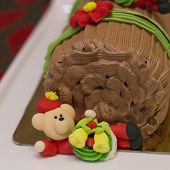 stock photo of yule  - Traditional Christmas Yule Log cake decorated with santa bear and fiower mazipan.