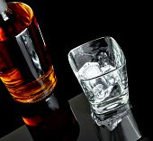 stock photo of whiskey  - top of view of empty whiskey glass with ice near bottle on black background with reflection - JPG