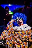 image of clowns  - Crazy ugly grunge evil clown in town on Halloween making people shock and scared - JPG