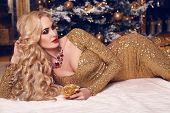 stock photo of beside  - fashion interior photo of beautiful sensual woman with blond hair in luxurious golden dress posing beside a Christmas tree - JPG