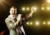 picture of microphone  - Young handsome businessman sining on stage in microphone - JPG