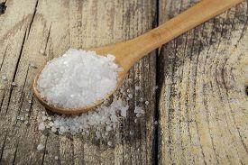 image of crystal salt  - Wood spoon full with salt crystals on old brown wood table - JPG