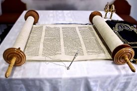 foto of scroll  - Torah scrolls are on the table with a stick read cape to scroll and kolokolchiki in Hebrew the ancient language picture sdelanaya close - JPG