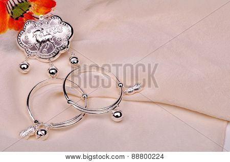 Silver Lock and Silver Bracelets on White Silk