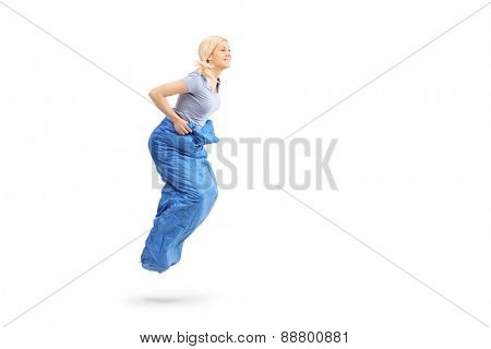 Profile shot of a young blond woman sack jumping in a blue sack isolated on white background