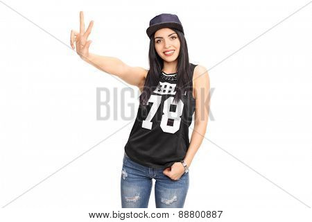 Beautiful young woman in a hip-hop outfit making a hand sign and looking at the camera isolated on white background