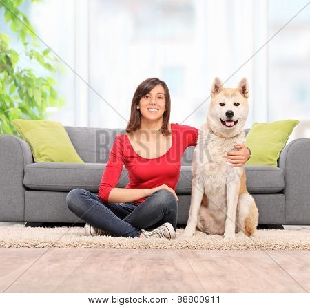 Young woman sitting on the floor with her Akita pet dog and looking at the camera in front of a gray sofa at home