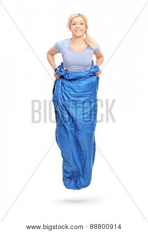 Vertical shot of a young blond woman jumping in a blue sack isolated on white background