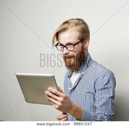Tehnology, education and lifestyle concept: young man  using a tablet computer - over gray background