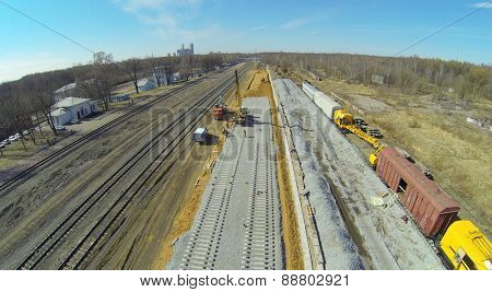 Workers are building the railroad tracks near the old tracks, aerial view