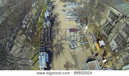 Car parts on the street next to the plant at spring day, aerial view
