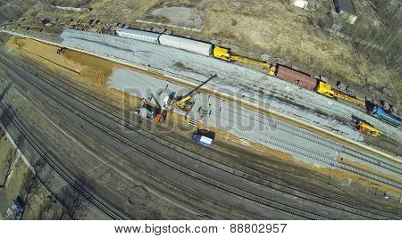 Construction equipment and workers at the construction site of new railways, aerial view