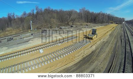 Compactor on the construction of the railway in a spring day, aerial view