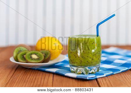 Healthy homemade kiwi juice in glass and fresh lemon, kiwifruit on light wooden background.