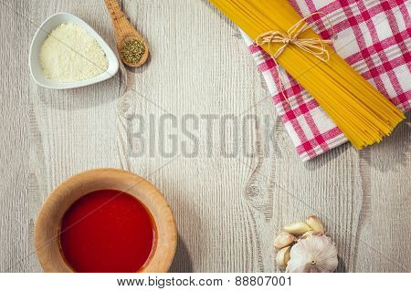 Close up of spaghetti and other ingredients, parmesan, oregano on kitchen table