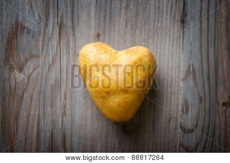 Heart shaped golden potato spud on Wooden Table Background, Concept and Idea of Food Cook Rustic Still life Style. Dramatic light table setting.