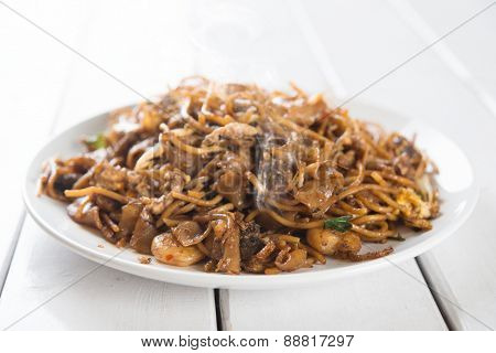 Stir fried char kuey teow over wooden background.  Fresh cooked with hot steams.