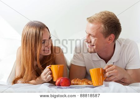 Couple Chatting And Eating In Bed