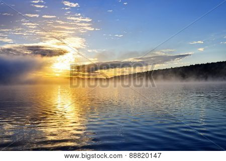 Sun rising over foggy lake in Algonquin Park, Canada