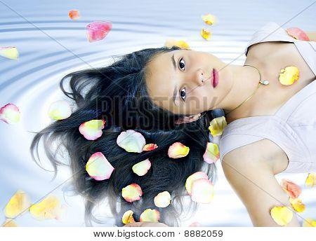 Linda chica en pétalos de rosas en el pelo en Spa