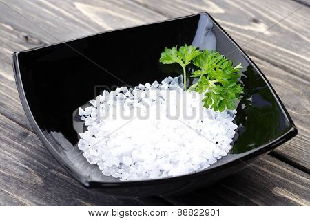 Salt in black bowl on wooden table