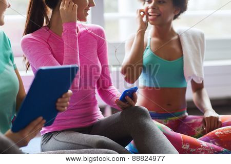 fitness, sport, technology and lifestyle concept - close up of happy women with smartphone, earphones and tablet pc computer listening to music in gym