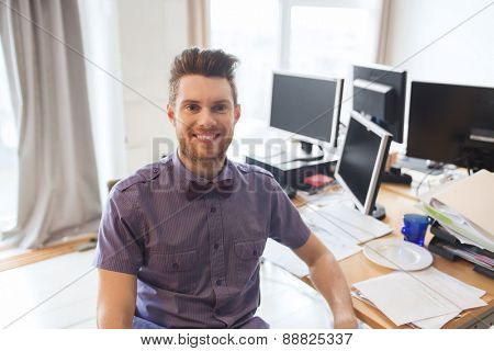 business, startup and people concept - happy businessman or creative male office worker with computers