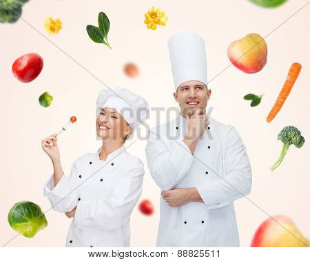 cooking, profession, inspiration, vegetarian diet and people concept - happy chef couple or cooks eating and thinking over beige background with falling vegetables