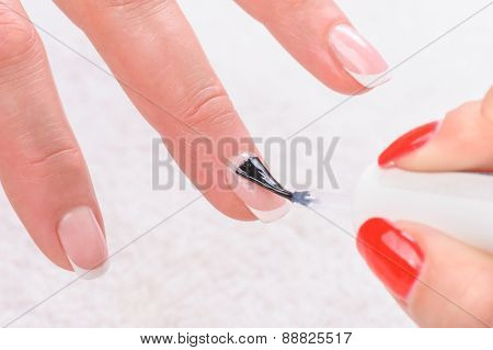 manicure applying, brushing fingernails with clear enamel