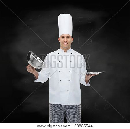 cooking, profession and people concept - happy male chef cook opening cloche cover over black chalk board background