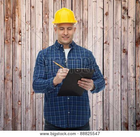 repair, construction, building, people and maintenance concept - smiling male builder or manual worker in helmet with clipboard taking notes over wooden fence background