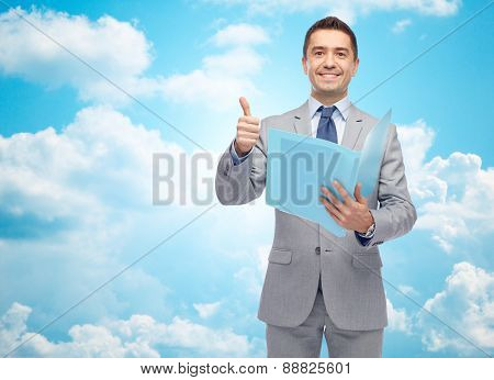 business, people, finances and paper work concept - happy smiling businessman in suit holding folder and showing thumbs up over blue sky with clouds background