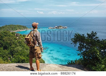 traveller with backpack standing on the rocks