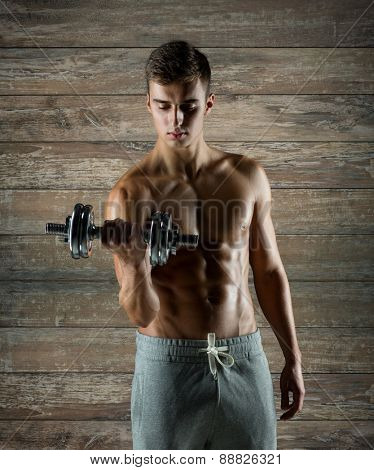 sport, fitness, weightlifting, bodybuilding and people concept - young man with dumbbell flexing biceps over wooden wall background