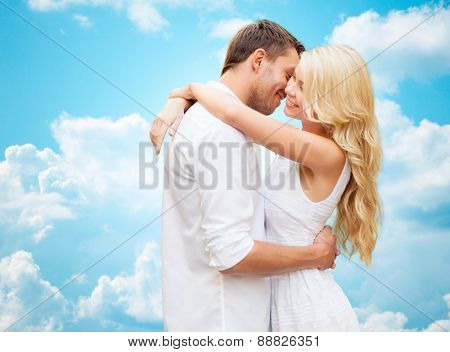 summer holidays, people, love and dating concept - happy couple hugging over blue sky and white clouds background