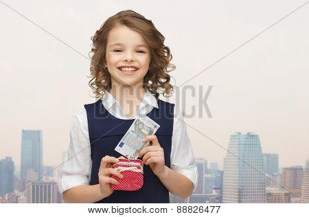 finances, childhood, people and savings concept - happy little girl with purse and paper euro money over city background