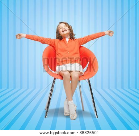 people, happiness, childhood and furniture concept - happy little girl sitting on chair with spreaded arms over blue striped background