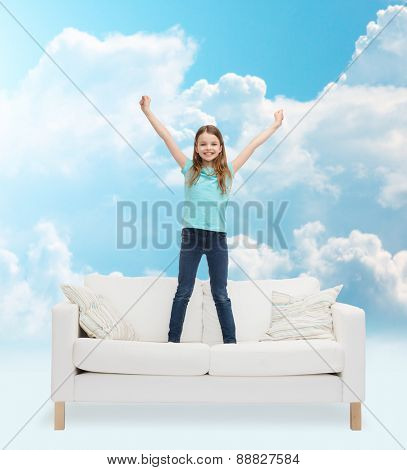 home, leisure, people and happiness concept - smiling little girl jumping on sofa over blue sky and white clouds background