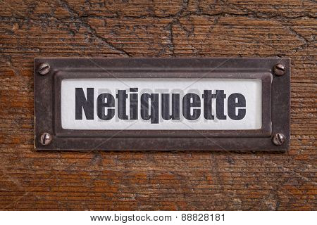 netiqutte (internet etiquette)  - file cabinet label, bronze holder against grunge and scratched wood