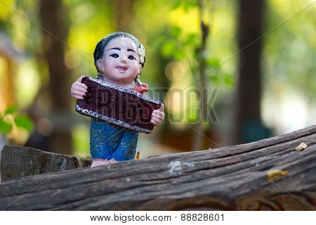 Funny Thai smiley figurine in a garden holding a placard