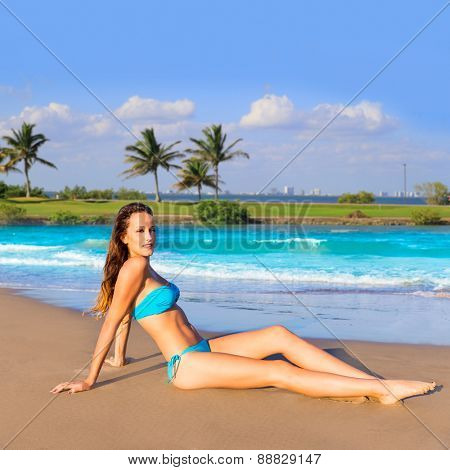Brunette tourist sitting in tropical beach sand tanning happy in summer vacation