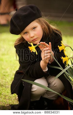 Serious Young Girl In Beret Stroking Daffodil