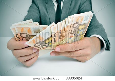 Sitting In A Desk Counting Euro Bills