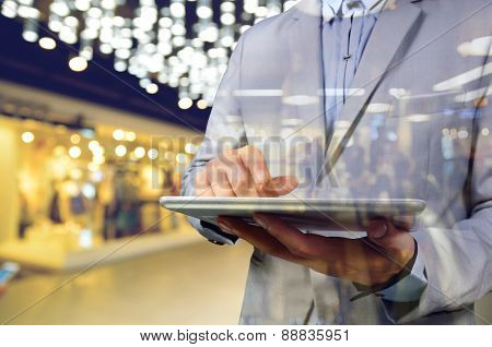 Business Man Using Mobile Digital Tablet In The Shopping Mall. Selective Focus On Tablet As Communic