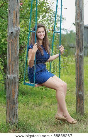 Portrait of brunette girl in navy blue sundress riding on handmade swing