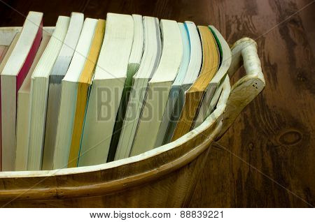 Books in the wooden basket. Vintage background