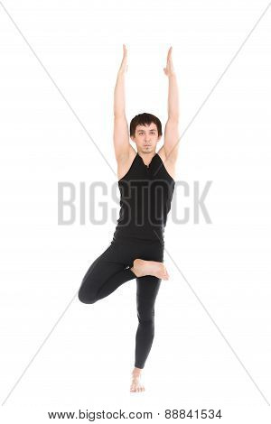 Sporty Young Man Standing In Tree Pose