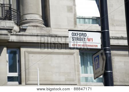 LONDON, UK - APRIL 22: Detail of Oxford Street sign next to a parking direction arrow on pole. April 22, 2015 in London. Oxford Street is the main commercial street in the city.